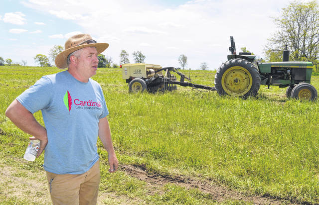 Cardinal Land Conservancy Executive Director Andy Dickerson, pictured, talks about what the future holds for Todd's Fork Preserve. In the background is a volunteer's tractor ready to pull a native grass seed drill loaned to Cardinal by the Ohio Department of Natural Resources Division of Wildlife at Fallsville.