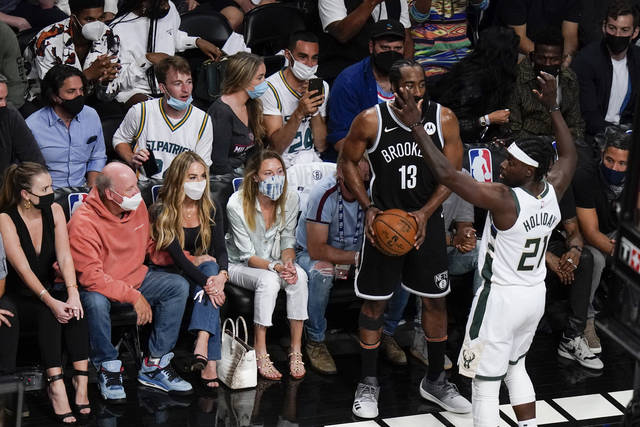 Fans watch as Milwaukee Bucks' Jrue Holiday (21) defends against Brooklyn Nets' James Harden (13) during the first half of Game 7 of a second-round NBA basketball playoff series Saturday, June 19, 2021, in New York. (AP Photo/Frank Franklin II)