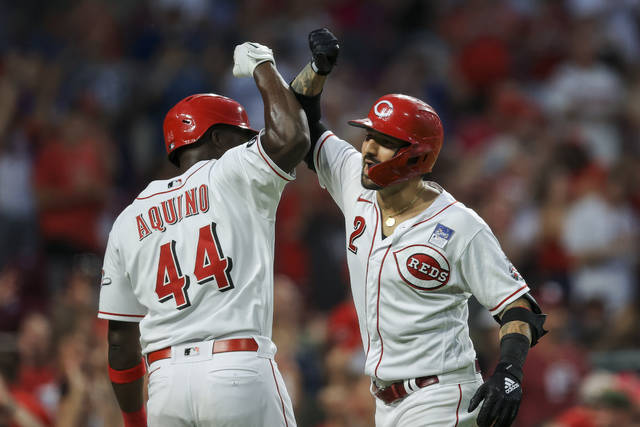 Cincinnati Reds' Nick Castellanos, right, celebrates with Aristides Aquino, left, after hitting a grand slam during the seventh inning of a baseball game against the Philadelphia Phillies in Cincinnati, Monday, June 28, 2021. (AP Photo/Aaron Doster)