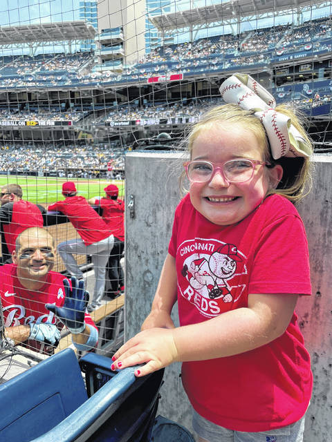 Abigail, the 6-year-old daughter of Fort Loramie graduate Kristin Courtney, takes a photo with her favorite baseball player, Cincinnati Reds first baseman Joey Votto, during a game Sunday at Petco Park in San Diego.