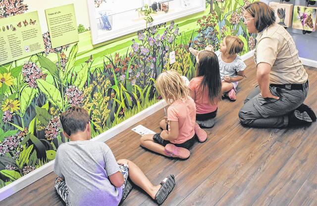 Park Naturalist Amanda Walski, far right, leads the kids in an activity identifying local flowers at the opening of the new nature center at Cowan Lake State Park.