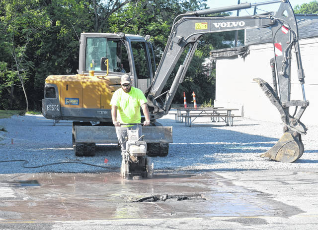 City workers clean up a broken storm sewer line on Sugartree Street on Thursday.