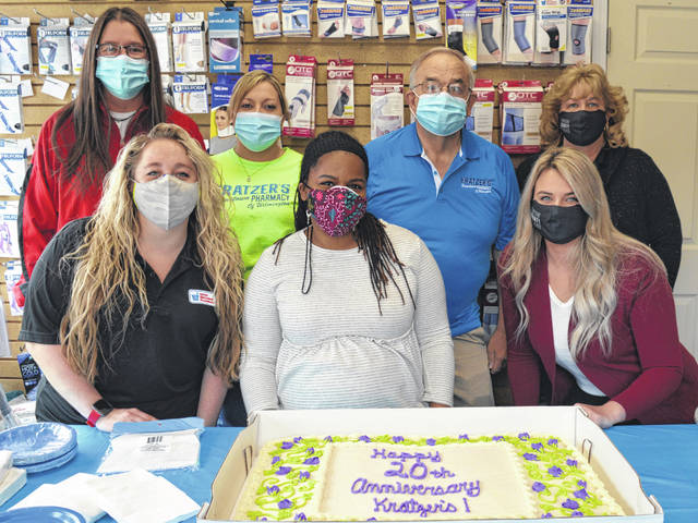 """Kratzer's Hometown Pharmacy on West Locust Street in Wilmington celebrated its 20th anniversary this spring with cake and punch and a prize drawing in which 20 people each won $100. Kratzer's staff gathered around the cake for a milestone photo. In the front from left are pharmacy tech Taylor Jaehnig, pharmacy tech manager Angela McKee, and University of Cincinnati graduated pharmacist Sydney Sodini; and in back from left are pharmacy tech Katrina Butcher, pharmacy tech Nina Hairfield, owner-operator Mark Kratzer, and accountant/bookkeeper Kathy Lawson. """"We hope to have many more anniversaries to come,"""" said Kratzer."""
