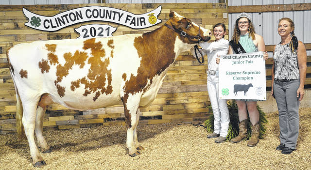For 2021 Reserve Champion Cow, winner is Paige Bauman, shown with Queen Shaleigh Duncan, and Judge Sherry B. Smith.