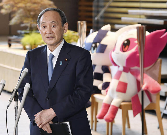 Japan's Prime Minister Yoshihide Suga speaks to media in front of the Olympics mascots at the prime minister's office in Tokyo, Thursday, July 1, 2021. Suga was still uncertain whether fans can be allowed at the Tokyo Olympics because of growing concern about rising COVID-19 cases on Thursday only three weeks before the games.(Kyodo News via AP)