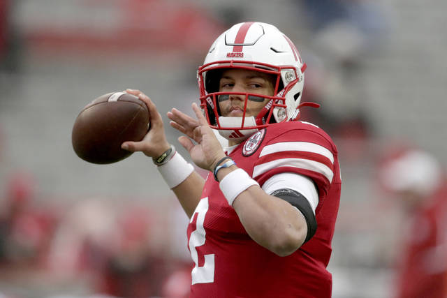 FILE - Nebraska quarterback Adrian Martinez warms up before an NCAA college football game against Iowa in Lincoln, Neb. in this Friday, Nov. 29, 2019, file photo. A new era in college sports has arrived. For the first time, NCAA athletes will be permitted to profit from their fame. Nebraska quarterback Adrian Martinez isn't a big social media guy, but he started thinking about ways to take advantage of the changes last fall. (AP Photo/Nati Harnik, File)