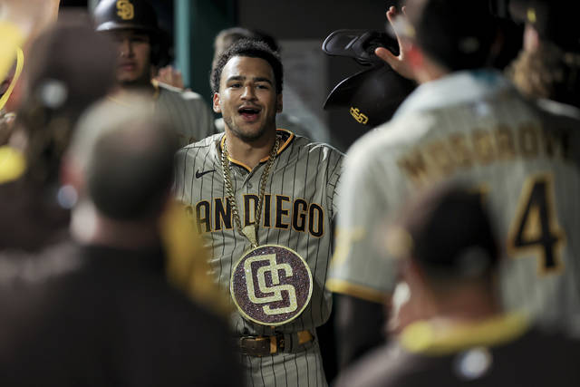 San Diego Padres' Trent Grisham celebrates with teammates after hitting a grand slam during the fifth inning of a baseball game against the Cincinnati Reds in Cincinnati, Wednesday, June 30, 2021. The home run is his second of the game. (AP Photo/Aaron Doster)