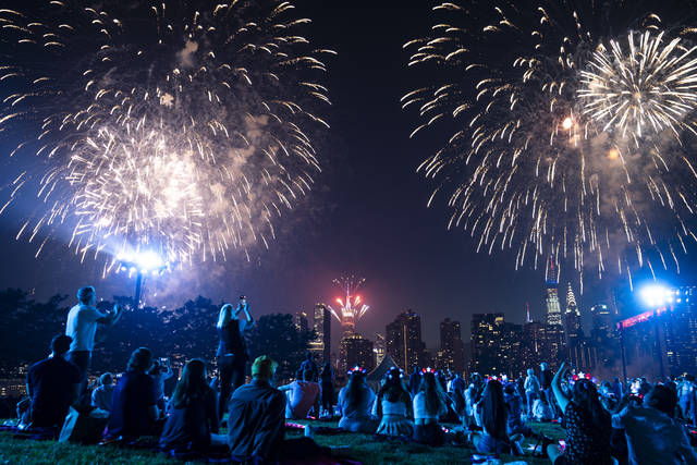 Spectators watch from the Queens borough of New York as fireworks are launched over the East River and the Empire State Building during the Macy's 4th of July Fireworks show, Sunday, July 4, 2021. (AP Photo/John Minchillo)