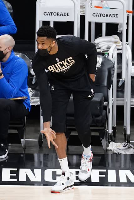 Injured Milwaukee Bucks forward Giannis Antetokounmpo reacts after a Milwaukee basket during the first half in Game 6 of the Eastern Conference finals in the NBA basketball playoffs against the Atlanta Hawks, Saturday, July 3, 2021, in Atlanta. (AP Photo/John Bazemore)