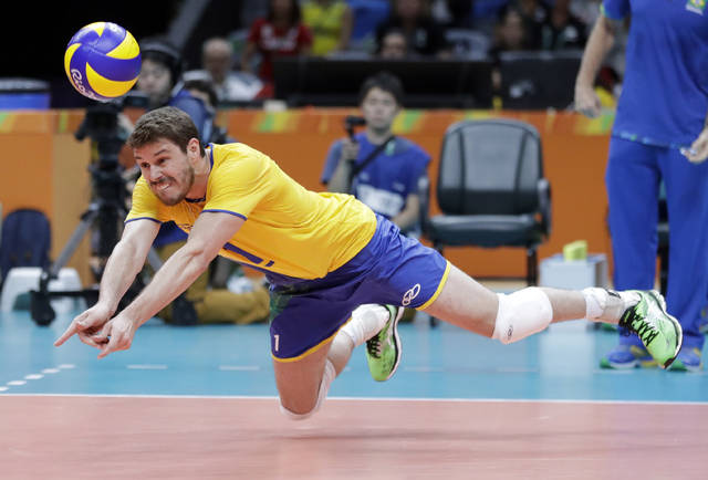 FILE - In this Aug. 9, 2016, file photo, Brazil's Bruno Rezende dives for the ball during a men's preliminary volleyball match against Canada at the Summer Olympics in Rio de Janeiro. Both defending champions in volleyball are in good position to contend for a repeat with Rezende back for a fourth Olympics for the Brazilian men after winning silver in 2008 and '12 and gold at home in Rio five years ago. (AP Photo/Jeff Roberson, File)