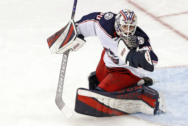 FILE - Columbus Blue Jackets goaltender Matiss Kivlenieks (80) has the puck in his hand as he makes a save during the third period of an NHL hockey game against the New York Rangers in New York, in this Sunday, Jan. 19, 2020, file photo. The Columbus Blue Jackets and Latvian Hockey Federation said Monday, July 5, 2021, that 24-year-old goaltender Matiss Kivlenieks has died. The team said in a statement Kivlenieks died from an apparent head injury in a fall after medical personnel arrived. It was not immediately clear what caused the fall or where he was at the time of the incident, and multiple messages were left with team and national federation personnel that were not immediately returned.( AP Photo/Kathy Willens, File)
