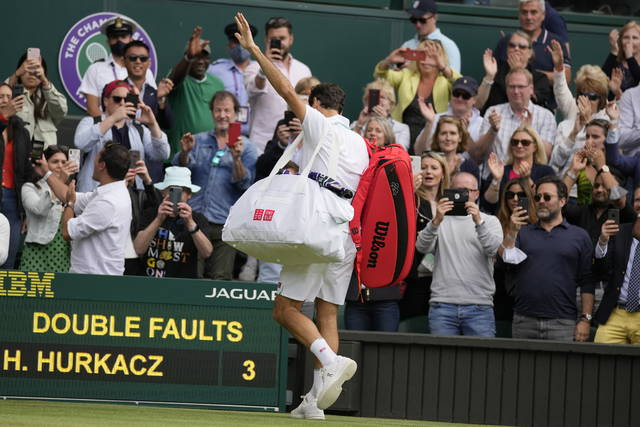 Switzerland's Roger Federer leaves the court after being defeated by Poland's Hubert Hurkacz during the men's singles quarterfinals match on day nine of the Wimbledon Tennis Championships in London, Wednesday, July 7, 2021. (AP Photo/Kirsty Wigglesworth)