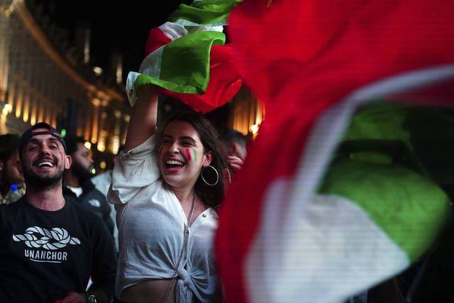Italy fans celebrate in Piccadilly Circus in central London after their team won the UEFA Euro 2020 Final against England, Sunday July 11, 2021. (Victoria Jones/PA Via AP)