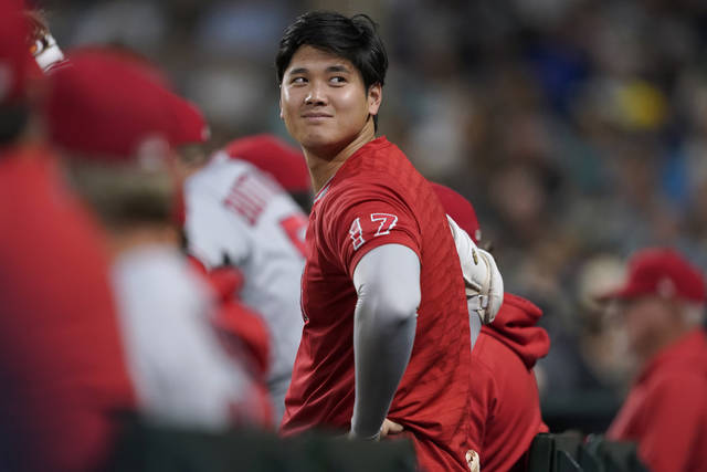 Los Angeles Angels' Shohei Ohtani looks out from the dugout during the sixth inning of the team's baseball game against the Seattle Mariners, Friday, July 9, 2021, in Seattle. (AP Photo/Ted S. Warren)