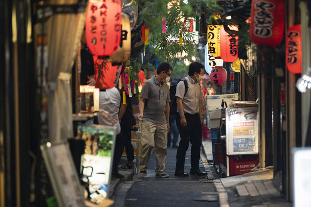 Men stop to check out a restaurant and bar in Tokyo on July 9, 2021. A state of emergency began Monday, July 12, 2021, in Tokyo, as the number of new cases is climbing fast and hospital beds are starting to fill just 11 days ahead of the Tokyo Olympics. (AP Photo/Hiro Komae)
