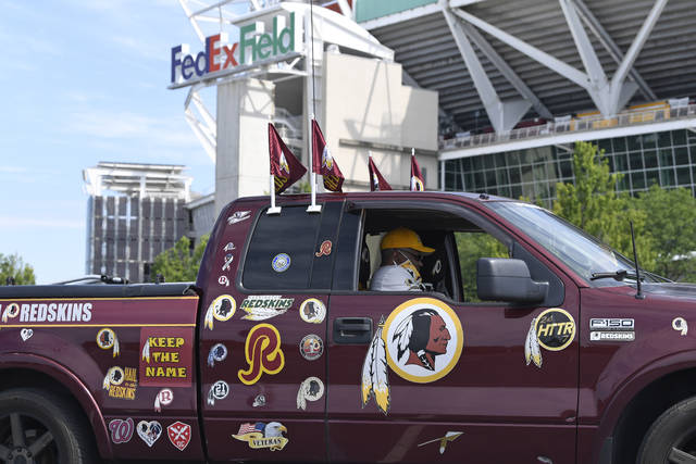 FILE - In this July 13, 2020, file photo, Rodney Johnson of Chesapeake, Va., sits in his truck outside FedEx Field in Landover, Md. Washington's NFL team will not be called the Warriors or have any other Native American imagery in the new name when it's revealed next year. (AP Photo/Susan Walsh, File)