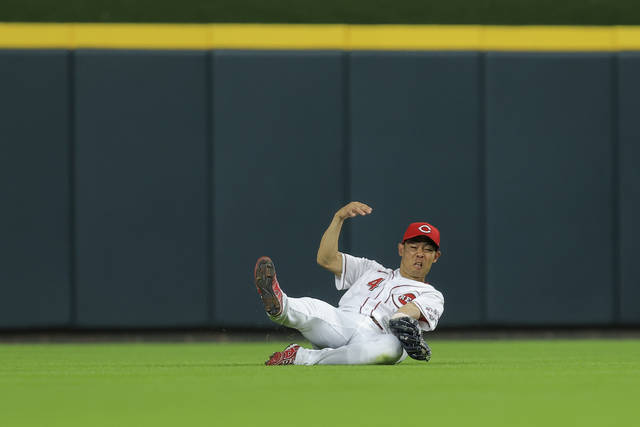 Cincinnati Reds' Shogo Akiyama slides to make a catch on a sacrifice fly hit by Milwaukee Brewers' Omar Narvaez during the seventh inning of a baseball game in Cincinnati, Saturday, July 17, 2021. (AP Photo/Aaron Doster)