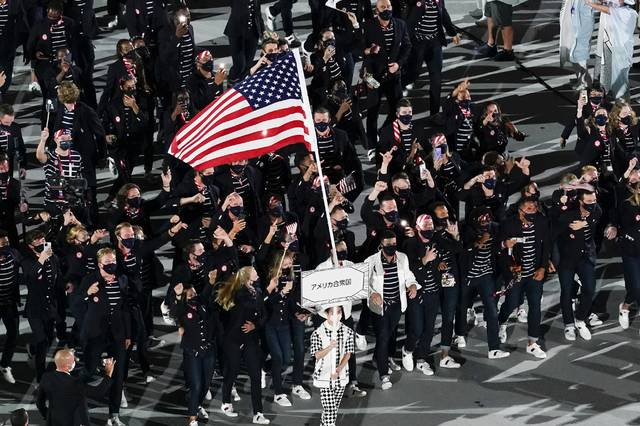 Sue Bird and Eddy Alvares, of the United States of America, carry their country's flag during the opening ceremony at the Olympic Stadium at the 2020 Summer Olympics, Friday, July 23, 2021, in Tokyo. (AP Photo/Morry Gash)