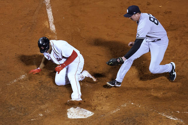 Boston Red Sox's Rafael Devers slides safely into home on a wild pitch by New York Yankees reliever Brooks Kriske (82), who cannot reach him with a tag in the 10th inning of a baseball game at Fenway Park, Thursday, July 22, 2021, in Boston. The Red Sox won 5-4. (AP Photo/Elise Amendola)