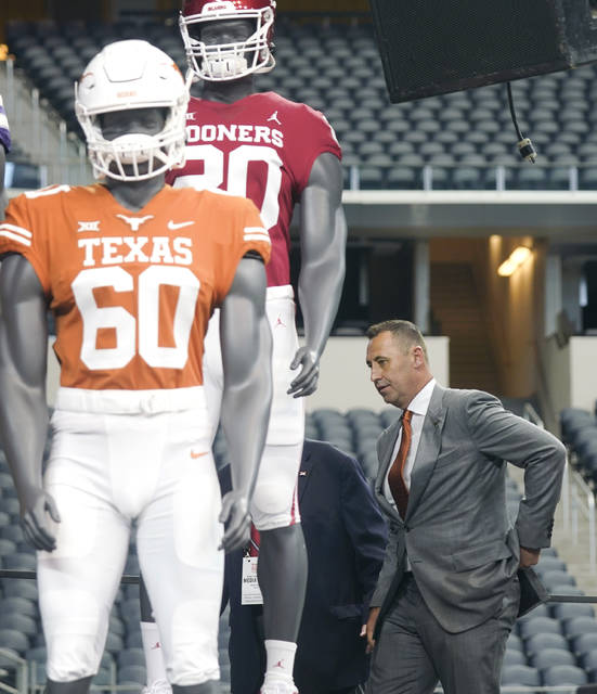 Texas head coach Steve Sarkisian walks on stage behind mannequins wearing Texas and Oklahoma uniforms during the NCAA college football Big 12 media days Thursday, July 15, 2021, in Arlington, Texas. (AP Photo/LM Otero)