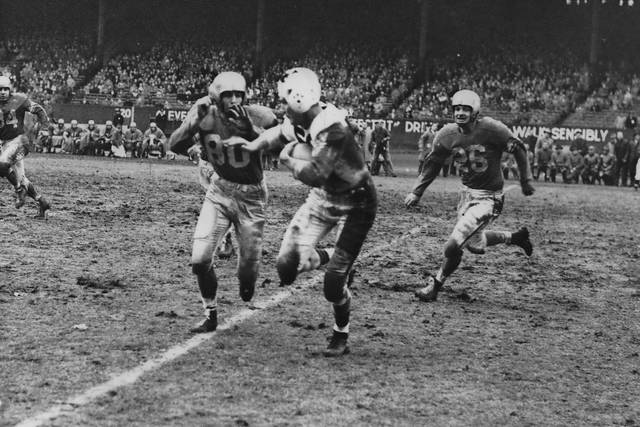 Cleveland Browns' Mac Speedie, foreground right, runs after making a catch for a first down before being tackled by an unidentified player, at left foreground, in this undated photo. At far right is Cleveland Browns' Hal Hering (26). Mac Speedie spent his life overcoming hurdles both physical and figurative. He's about to clear another. A quick, sure-handed wide receiver on powerhouse Cleveland Browns teams in the 1940s and 50s, Speedie, who overcame a childhood disease and later delayed his playing career to serve in World War II, is finally being inducted into the Pro Football Hall of Fame. (Cleveland.com via AP)