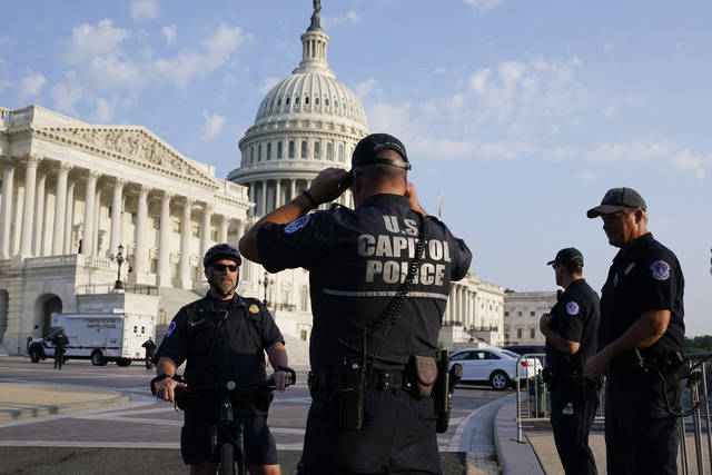 The U.S. Capitol is seen in Washington, early Tuesday, July 27, 2021, as U.S. Capitol Police watch the perimeter. Democrats are launching their investigation into the Jan. 6 Capitol insurrection. They're beginning with a focus on the law enforcement officers who were attacked and beaten as the rioters broke into the building. It's an effort to put a human face on the violence of the day. The police officers who are testifying Tuesday endured some of the worst of the brutality. The panel's first hearing comes as partisan tensions have only worsened since the insurrection. Many Republicans have played down or outright denied the violence that occurred and denounced the Democratic-led investigation as politically motivated. (AP Photo/J. Scott Applewhite)
