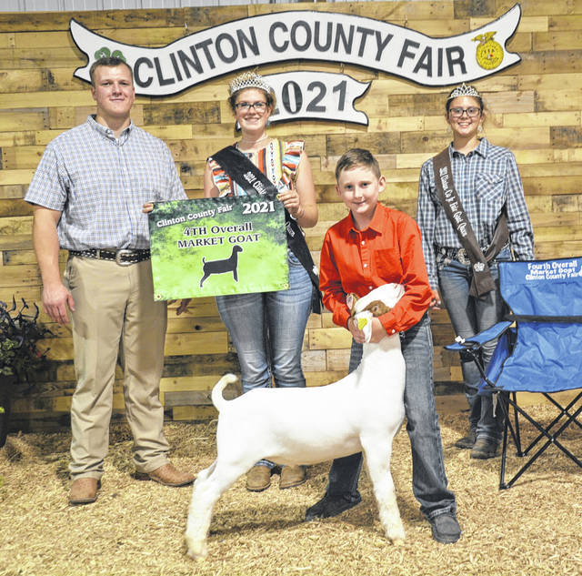 For fourth place Overall Market Goat at the 2021 fair, shown are Judge Luke Wechter, Fair Queen Shaleigh Duncan, winner Cole Stump, and Goat Queen McKinzey DeBord.