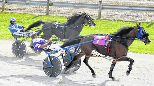 Armour Cruiser (right) closed with a flourish, rallying from fourth place with a quarter mile to go to reach the winner's circle in the fourth race Monday at the Clinton County Fair.
