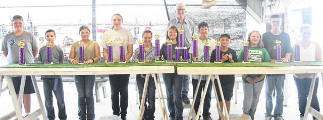 The 2021 Clinton County Fair Open Youth Rabbit Show winners include: from left, Jace and Jayden Doyle, Hunter Vaughn, Haley Hinkle, Carolyn Koch, Hannah Gerard, Shelby Newton, show judge Chris Hayhow (in back), Gabe Stewart, Gage and Peyton Branderburg, Gracie Goodwin, Eli Caldwell, and Emily Goodwin. Not shown are Phillip and Robert Greenwood.