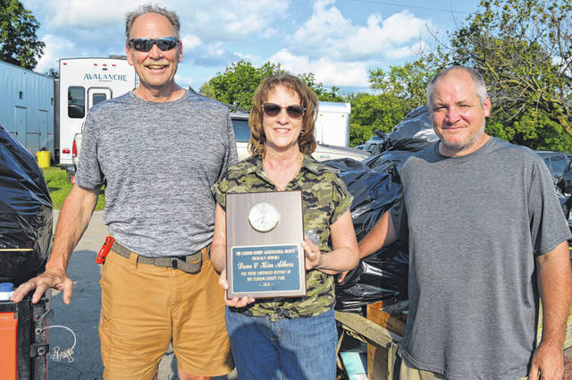 """From left, Dave and Kim Albers and crew member Shawn Hartley, were recognized as Clinton County Fair Business Honorees for their longtime support of the county fair as the cleanup crew. The Alberses have performed cleanup duties during 22 consecutive fairs, while Hartley has assisted for 14 summers. Among other things, cleaning up trash is key in keeping uninvited bees and flies from the festivities. Clinton County Agricultural Society member Mike Hacker said the crew """"went above and beyond"""" last summer in addressing COVID-19 concerns. The annual eight-day event draws thousands of people to the fairgrounds. Dave said a Wilmington sanitation worker told him the fair averages 250 cubic yards of garbage per year."""