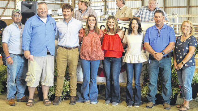 The recipients of the Lois Boyer Leadership Scholarship were introduced prior to the Junior Fair's livestock sale of champions. In the photo are committee members who interviewed the candidates and the youth themselves. From left are committee members Brad Woodruff and Billy Arehart, the main scholarship recipient Colton Doyle, and the other scholarship recipients Gracee Stewart, Paige Bryant and Marci Ellis, plus committee members Scot Gerber and Anne Foxworthy.