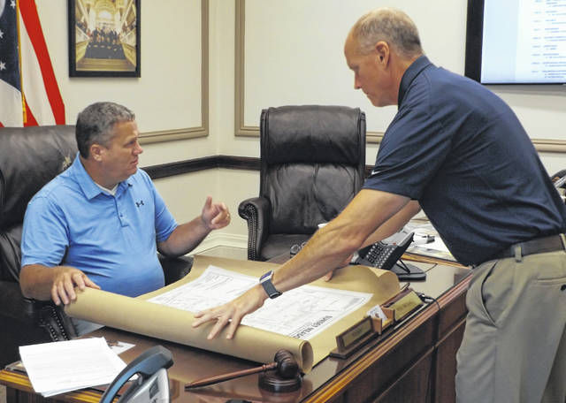 Land owner Tony Russell, right, places a real estate plat upon the desk of Clinton County Commissioners President Mike McCarty, left, for the purpose of signatures.