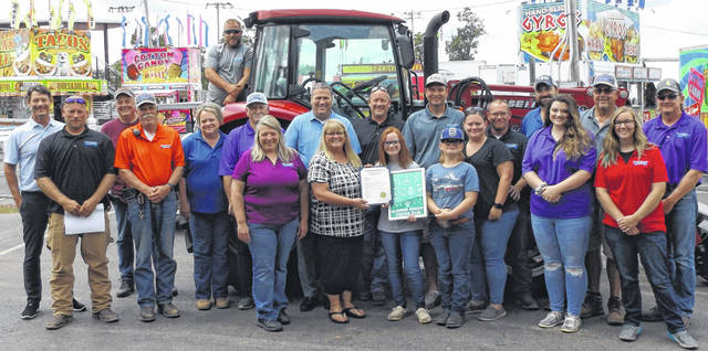 Following a joint meeting Wednesday of the Board of Clinton County Commissioners and members of the Fair Board that was held at the fairgrounds, folks gathered outside for a group photo. Front and center are Clinton County Commissioner Brenda Woods holding a proclamation recognizing East Clinton 8th-grader Kayleigh Vance, next to Woods, who won a Junior Fair T-shirt design contest involving multiple counties. Also pictured are Vance's family, fairgrounds office staff and fairgrounds caretakers.