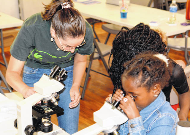 WC junior Kelsey Merriman shows Mayonie the magical world that can be viewed through a microscope.