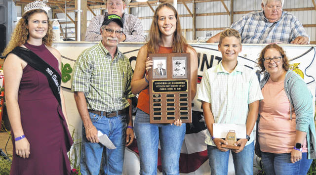 Lawrence Dean & Gary Quallen Memorial Outstanding Dairy Exhibitor Awards were presented to winners in the senior and junior age divisions. From left, standing in the photo foreground are Clinton County Junior Fair Queen Shaleigh Duncan, Jim Wilson, Outstanding Dairy Exhibitor senior division honoree Caili Baumann, Outstanding Dairy Exhibitor junior division honoree Ian Danku, and Jennifer Buckley.