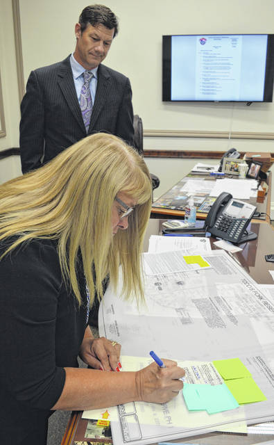 Official papers for the new Todd's Fork Reserve residential development is signed this week by Clinton County Commissioner Brenda Woods, foreground, as Commissioner Kerry Steed waits to add his signature.