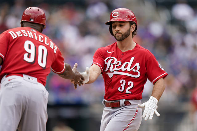 Cincinnati Reds' Max Schrock (32) celebrates with first base coach Delino DeShields (90) after hitting a single during the seventh inning of a baseball game against the New York Mets, Sunday, Aug. 1, 2021, in New York. (AP Photo/Corey Sipkin)