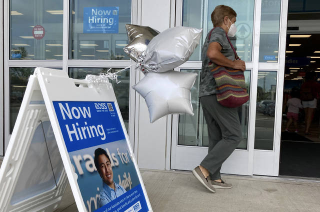 A shopper passes a hiring sign while entering a retail store in Morton Grove, Ill., Wednesday, July 21, 2021. Despite an uptick in COVID-19 cases and a shortage of available workers, the U.S. economy likely enjoyed a burst of job growth last month as it bounces back with surprising vigor from last year's coronavirus shutdown. The Labor Department's July jobs report Friday, Aug. 6 is expected to show that the United States added more than 860,000 jobs in July, topping June's 850,000, according to a survey of economists by the data firm FactSet.   (AP Photo/Nam Y. Huh)