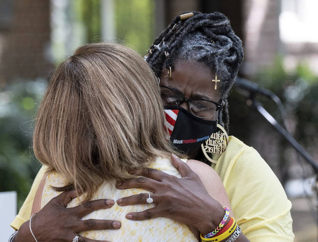 Marjorie Roberts, right, hugs Tanya Washington after speaking about how COVID effected her during a gathering at St. Luke's Episcopal Church in Atlanta on Saturday, Aug. 7, 2021, as part of National COVID Awareness Day.  (Ben Gray/Atlanta Journal-Constitution via AP)