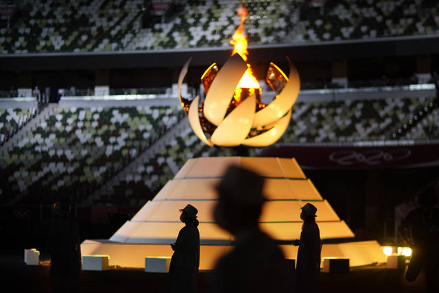 Volunteers stand as International Olympic Committee's President Thomas Bach gives a speech during the closing ceremony in the Olympic Stadium at the 2020 Summer Olympics, Sunday, Aug. 8, 2021, in Tokyo, Japan. (AP Photo/David Goldman)