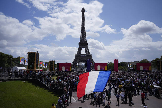 A man unfurls a French flag at the Olympics fan zone at Trocadero Gardens in front of the Eiffel Tower in Paris, Sunday, Aug. 8, 2021. A giant flag will be unfurled on the Eiffel Tower in Paris Sunday as part of the handover ceremony of Tokyo 2020 to Paris 2024, as Paris will be the next Summer Games host in 2024. The passing of the hosting baton will be split between the Olympic Stadium in Tokyo and a public party and concert in Paris. (AP Photo/Francois Mori)