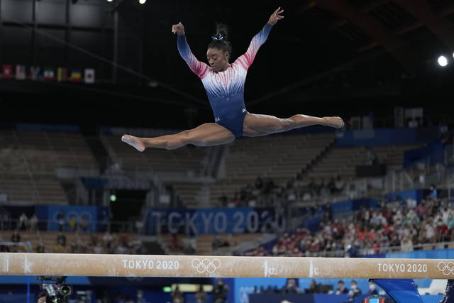 FILE - Simone Biles performs on the balance beam during the artistic gymnastics women's apparatus final at the 2020 Summer Olympics in Tokyo, in this Tuesday, Aug. 3, 2021, file photo. Biles is at peace with her decision to opt out of several competitions at the Tokyo Olympics to focus on her mental health. The seven-time Olympic medalist is happy to spread the importance of putting the person ahead of the athlete, one of the themes of her fall exhibition tour that will feature four other members of the 2021 Olympic gymnastics team. (AP Photo/Ashley Landis)