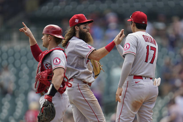 Los Angeles Angels catcher Max Stassi, from left, Brandon Marsh and Shohei Ohtani (17) celebrate after beating the Detroit Tigers 13-10 in a baseball game in Detroit, Thursday, Aug. 19, 2021. (AP Photo/Paul Sancya)