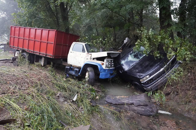 A truck and a car sit in a creek Sunday, Aug. 22, 2021, after they were washed away the day before in McEwen, Tenn. Heavy rains caused flooding in Middle Tennessee and have resulted in multiple deaths as homes and rural roads were washed away. (AP Photo/Mark Humphrey)