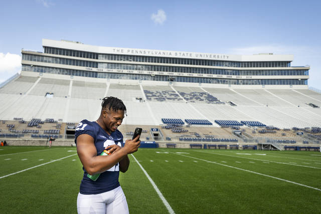 Penn State running back Noah Cain makes a call during photo day for the NCAA college football team Saturday, Aug. 21, 2021, in State College, Pa. (Joe Hermitt/The Patriot-News via AP)