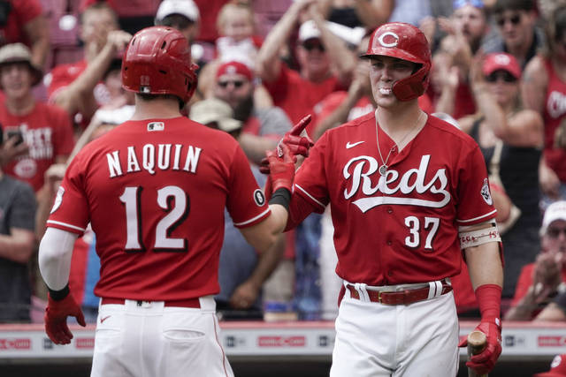 Cincinnati Reds' Tyler Naquin (12) celebrates with Tyler Stephenson (37) after hitting a solo home run during the first inning of a baseball game against the Miami Marlins, Sunday, Aug. 22, 2021, in Cincinnati. (AP Photo/Jeff Dean)