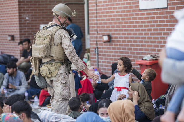 In this Aug. 21, 2021, photo provided by the U.S. Marine Corps, a Marine with Special Purpose Marine Air-Ground Task Force-Crisis Response-Central Command (SPMAGTF-CR-CC) provides fresh water to a child during an evacuation at Hamid Karzai International Airport in Kabul, Afghanistan. (Sgt. Samuel Ruiz/U.S. Marine Corps via AP)