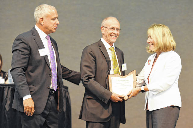 Monte Anderson (center) is formally inducted onto the Ohio Agricultural Hall of Fame by Mike Bumgarner, president of the Ohio Agricultural Council, and Dr. Catherine Kress, vice president for agricultural administration at Ohio State University.