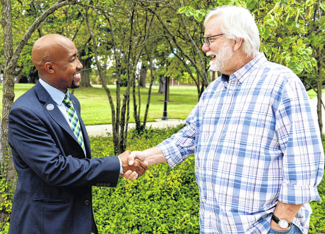 President Trevor Bates, left, congratulates and thanks J. Wynn Alexander for his 35 years of service to the College.