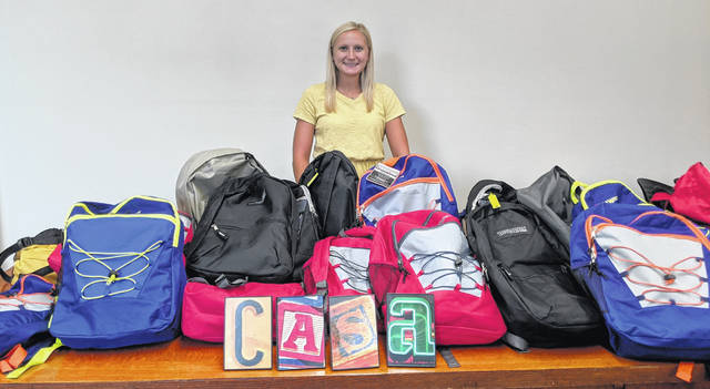 Tarah Mongold with the book bags and supplies.